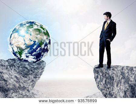 Businessman standing on the edge of mountain with a globe on the other side