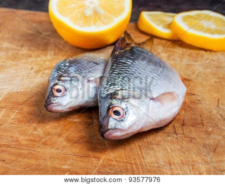Raw fish with lemon on the cutting board