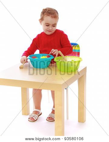 Girl in kindergarten playing artificial fruit sitting at the tab