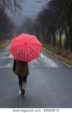 Rainy day woman holding red umbrella