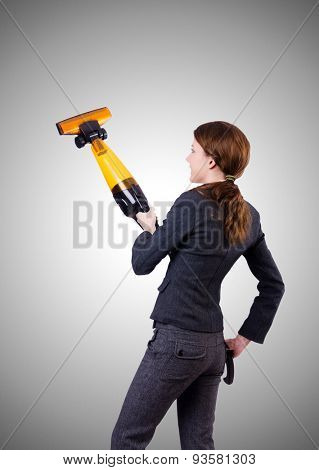 Young woman with vacuum cleaner against gradient