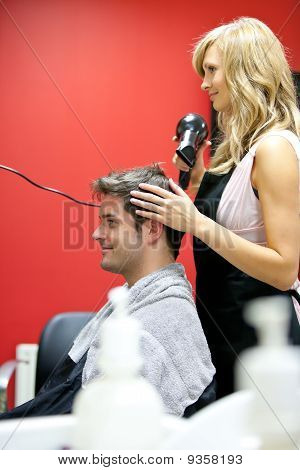 Blond Hairdresser Drying Her Customer's Hair