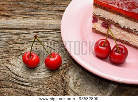 Cherry cake and cherry on wooden background