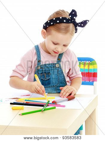 Little girl in denim overalls and a bandage on his head draws wi