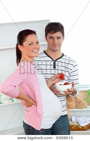 Porträt einer lächelnden schwangeren Frau Essen Erdbeeren und ihres Mannes