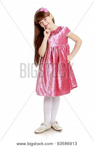 Stylish long-haired little girl in a red velvet dress and white