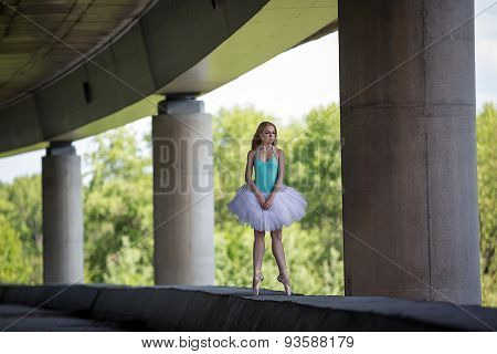 Graceful ballerina doing dance exercises on a concrete bridge