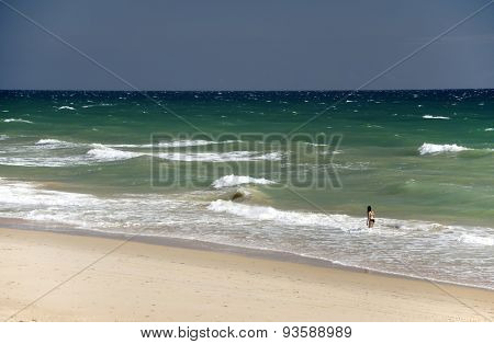 Young girl enjoying the waves of the Atlantic Ocean in Algarve, Portugal, Europe