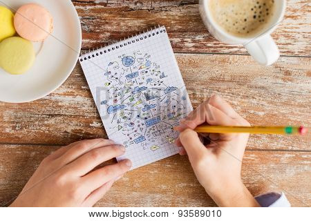 business, education, planning and people concept - close up of female hands with pencil, coffee and cookies drawing scheme to notebook on table