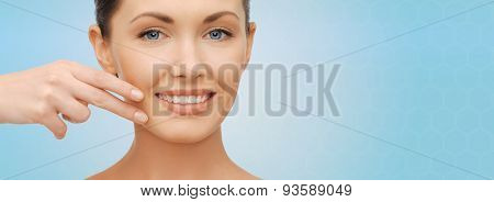 healthcare, people and beauty concept - beautiful woman touching her face skin over blue background