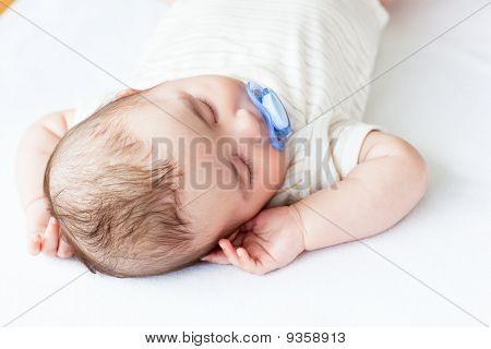 Portrait Of An Adorable Baby With A Pacifier Sleeping In A Bed