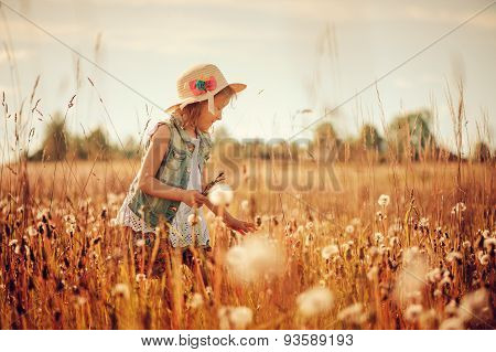 happy child girl in straw plays with blow balls on summer sunny field