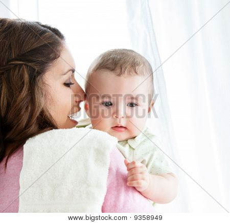 Cheerful Young Mother Taking Care Of Her Adorable Baby