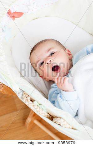 Portrait Of A Lively Baby Lying In His Cradle