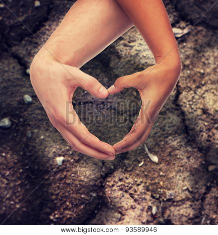 love, care, hope and charity concept - closeup of woman and man hands showing heart shape over ground background