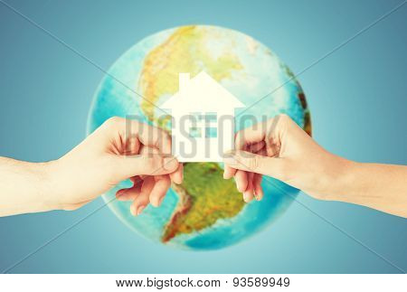 people, home, ecology and land resources saving concept - closeup of woman and man hands holding green paper house over earth globe and blue background