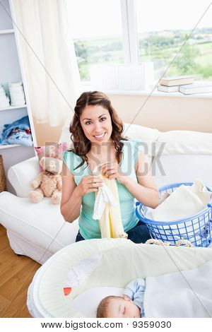 Cheerful Young Mother Doing The Laundry While Her Baby Is Sleeping In The Living-room