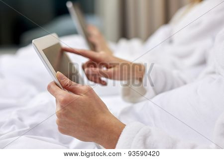 travel, tourism, people and technology concept - close up of woman hands in bathrobe with tablet pc computer at hotel