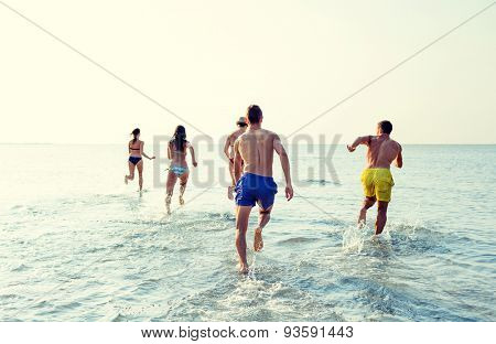 friendship, sea, summer vacation, holidays and people concept - group of smiling friends in swimwear running on beach from back