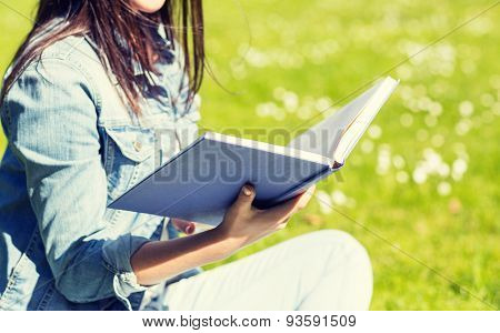 lifestyle, summer vacation, education, literature and people concept - close up of smiling young girl reading book and sitting on grass in park