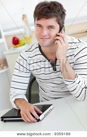 Attractive Man Talking On Phone Using His Laptop In The Kitchen