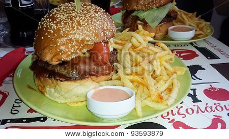 Huge Hamburger With Fried Poratoes And Sauce