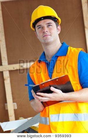 Thoughtful Male Worker Holding A Clipboard