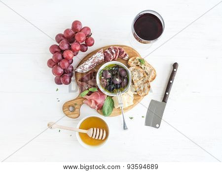 Wine appetizer set. Glass of red, grapes, parmesan cheese, meat variety, bread slices, pecan nuts, h