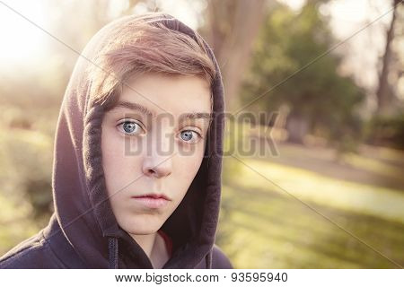 Portrait Of A Teenage Boy With Black Hoodie In A Park