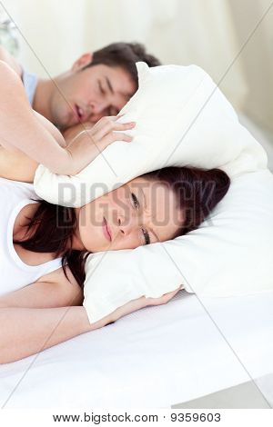 Young Woman Annoyed By The Snores Of Her Boyfriend In The Bedroom