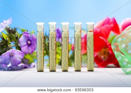 Five Small Glass Tubes With Homeopathy Globules, Blue Background And Flowers