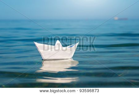 Paper toy ship and deep blue sea. Conceptual design.
