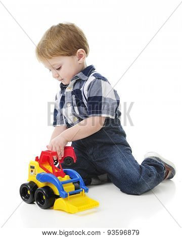 An adorable 2-year-old playing on the floor with a toy front loader.  On a white background.