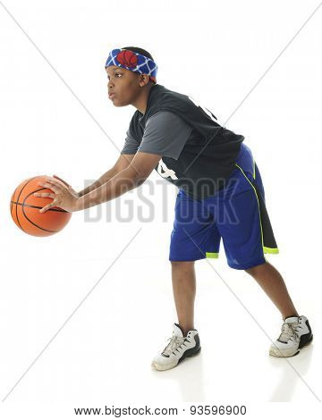 A tween African American athlete ready to pass a basketball.   On a white background.