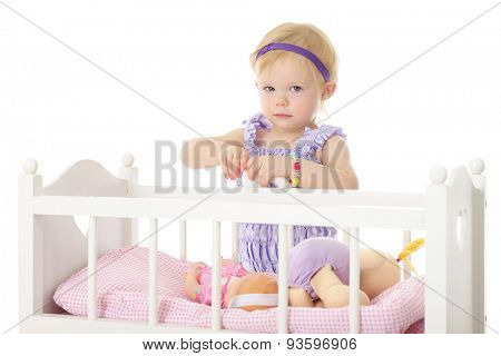 An adorable 2-year-old holding a baby bottle in her hands while standing by her doll crib containing two dolls.  On a white background.