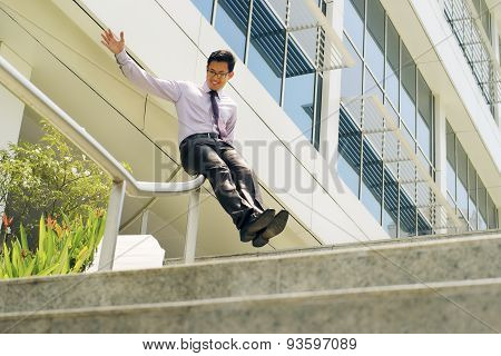 Chinese Businessman Going Downstairs Sliding On Rail For Joy