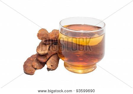 Tamarind juice in a glass surrounded by fresh ripe tamarinds