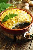 image of nettle  - Potato casserole with meat and nettle on the table - JPG