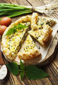 picture of nettle  - Pie with nettles and spring onion on the table - JPG