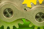 pic of kinetic  - Partial closeup macro image of detached metal brass shiny cogwheel machinery mechanical element on vibrant background colorful set of green and yellow surface paper - JPG