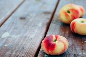 stock photo of saturn  - Fresh Saturn peaches on old wooden background - JPG