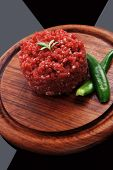 foto of hamburger-steak  - very big raw hamburger cutlet with sprouts and chilli pepper on wooden plate over black background - JPG