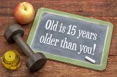 Постер, плакат: Old is 15 years older than you  slate blackboard sign against weathered red painted barn wood wit