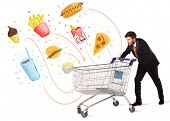 image of junk  - Businessman pushing a shopping cart and toxic junk food and cigarettes coming out of it - JPG
