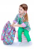picture of little school girl  - The little girl takes the book out of the school satchel  - JPG