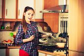 stock photo of stir fry  - Woman in kitchen cooking stir fry frozen vegetables and tasting - JPG