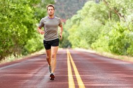 pic of fitness man body  - Sport and fitness runner man running on road training for marathon run doing high intensity interval training sprint workout outdoors in summer - JPG