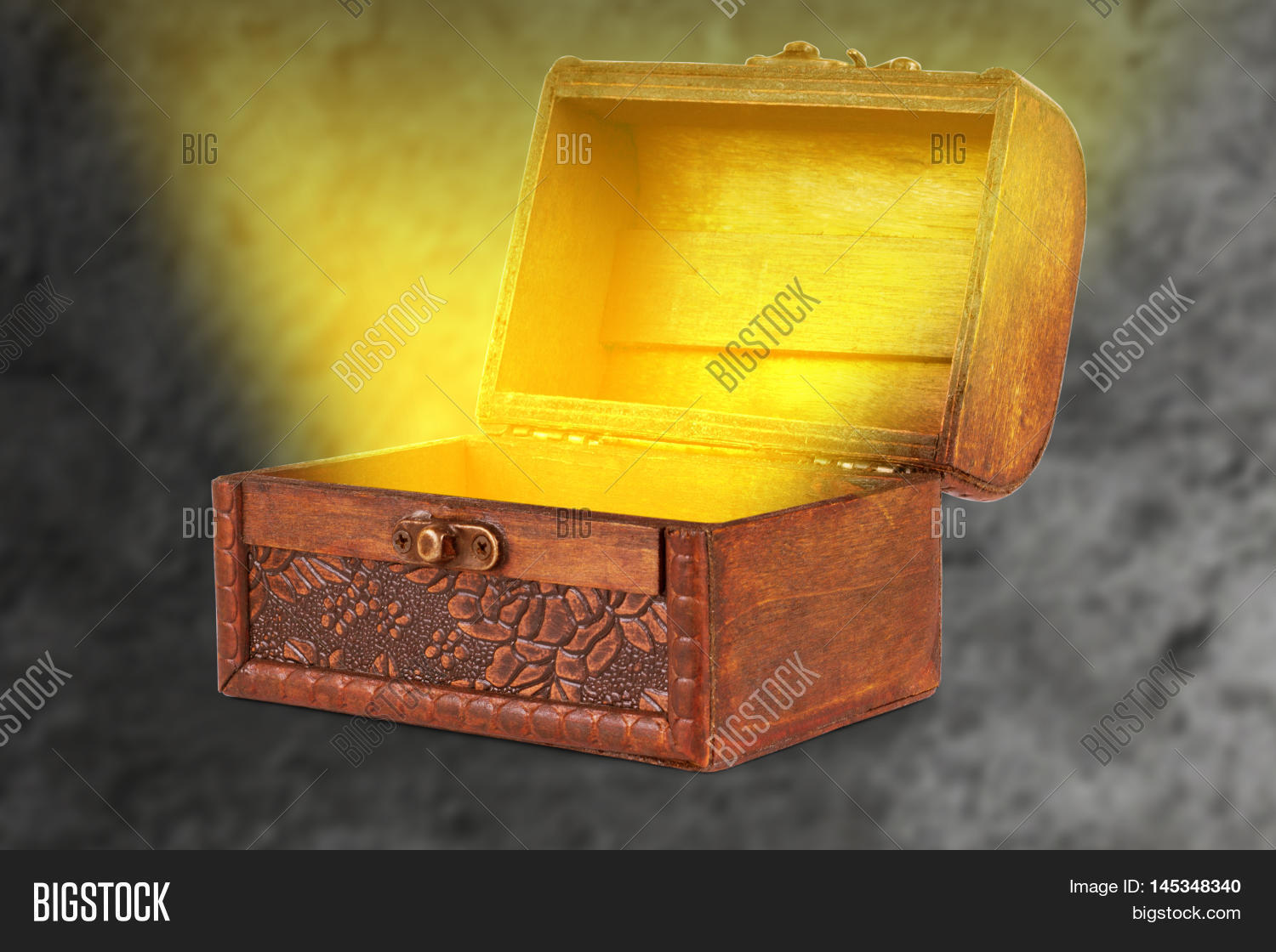 wooden treasure chest with a magical wispy light coming out of the box on a black