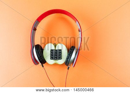 Alphanumeric apple and earphones on orange background