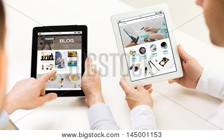 business, people, technology, blogging and online shopping concept - close up of businessman hands with blog and internet shop page on tablet pc computer screens at office